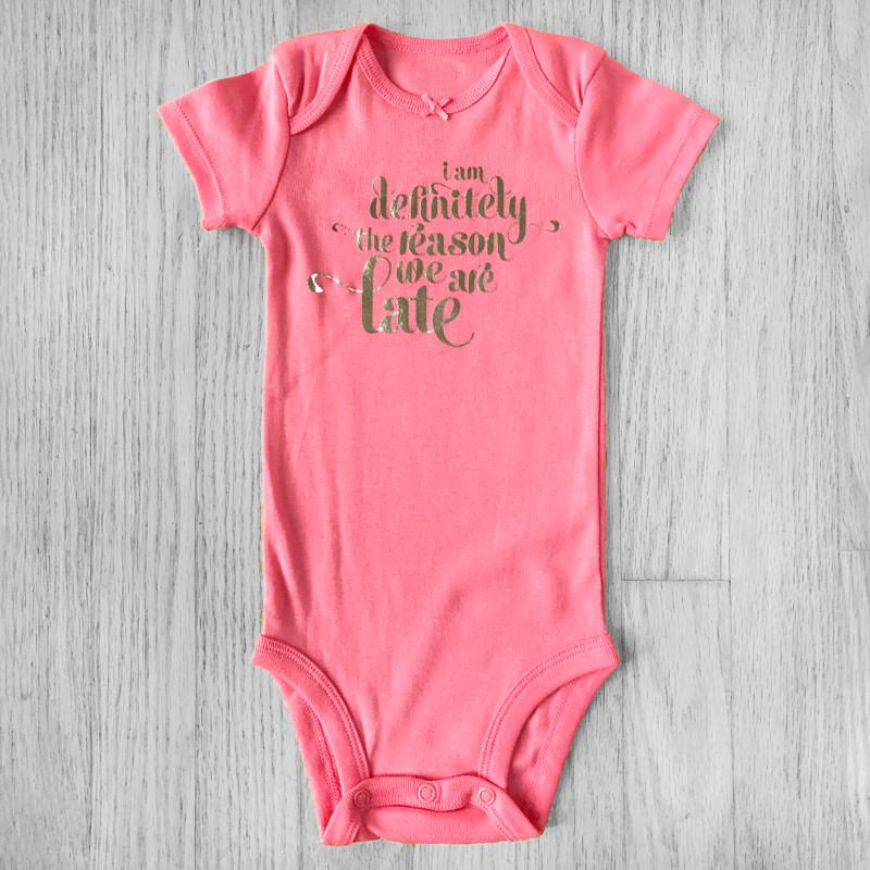 I am Definitely the Reason We Are Late Metallic Silver Lettering Baby Bodysuit